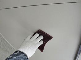 軒裏天井も、古い塗膜や汚れを落とすため、まずは金属ヘラで削り、細かい破片はナイロンスポンジでケレン清掃します。